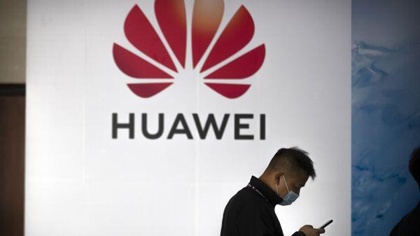 Una persona camina delante del logotipo de Huawei en una feria tecnológica en Pekín - Sputnik Mundo