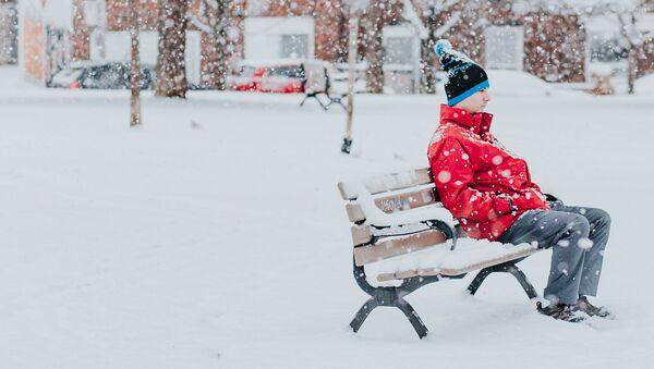 Una persona sentada en un banco durante una nevada - Sputnik Mundo