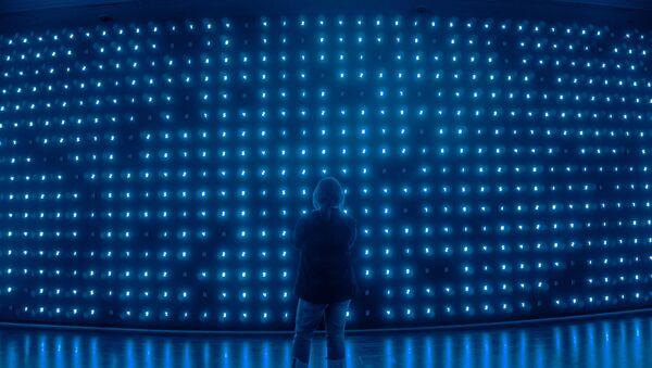 Una mujer delante de un panel de luces - Sputnik Mundo