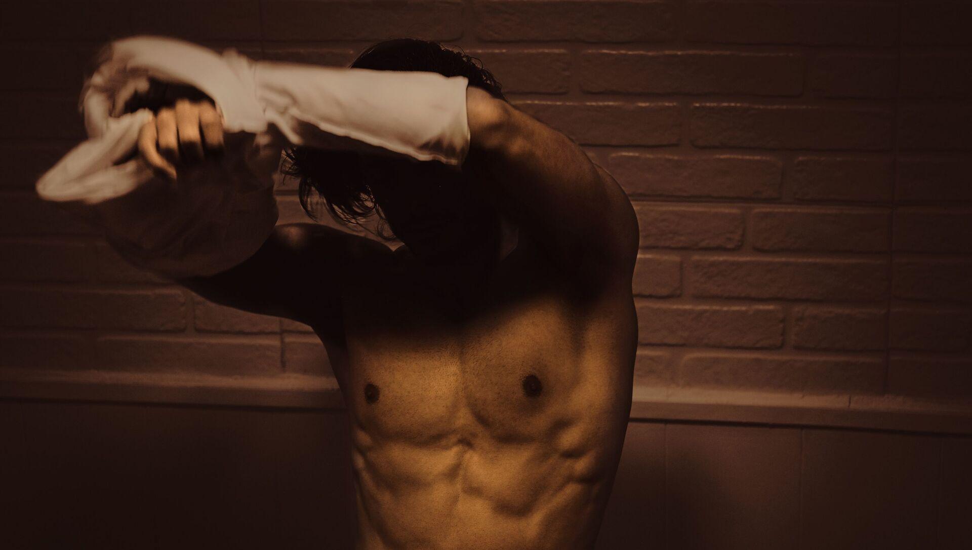 Un hombre se quita la camisa - Sputnik Mundo, 1920, 08.11.2020