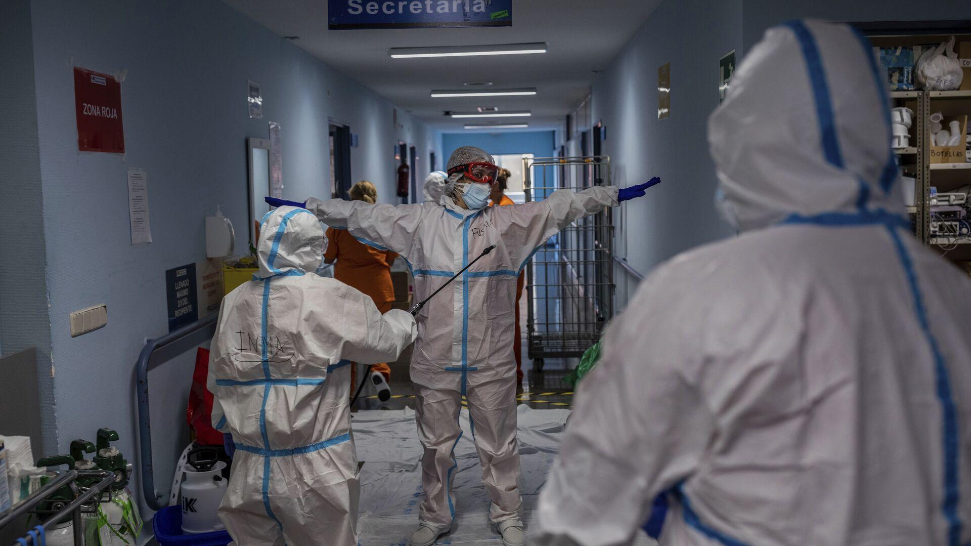 Un miembro del equipo médico es desinfectado antes de salir de la sala COVID-19 del hospital Severo Ochoa en Leganés, en las afueras de Madrid, España.  - Sputnik Mundo, 1920, 25.03.2021
