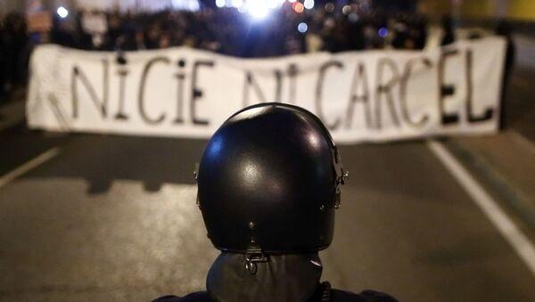 Un oficial de la policía antidisturbios hace guardia mientras los manifestantes marchan con una pancarta que dice No a los CIE, no a las cárceles - Sputnik Mundo