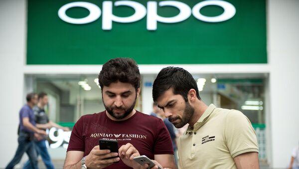 Dos personas con teléfonos inteligentes enfrente de la tiendad de Oppo en Shenzhen - Sputnik Mundo