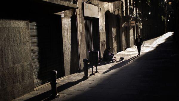 Una mujer pasa junto a un hombre que pide limosna en una calle del centro de Barcelona - Sputnik Mundo