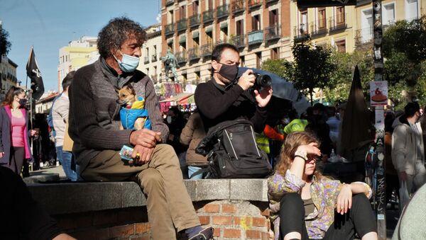 Varias personas reposan en la Plaza de Cascorro de Madrid durante el primer domingo del Rastro - Sputnik Mundo