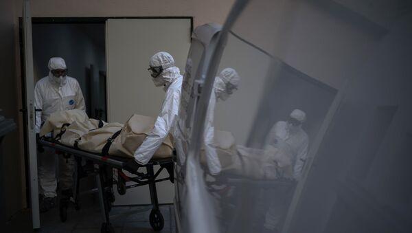 Trabajadores de una morgue recogen el cuerpo de una víctima de COVID-19 de un hogar de mayores en Barcelona, España.  - Sputnik Mundo