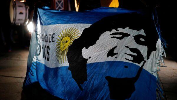 Una bandera de Argentina con el retrado de Maradona - Sputnik Mundo