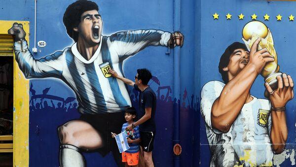 Болельщик с сыном скорбит по Диего Марадоне в Аргентине  - Sputnik Mundo