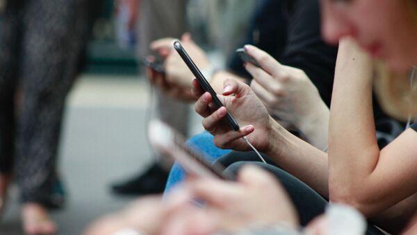 Unas personas utilizan sus teléfonos móviles - Sputnik Mundo
