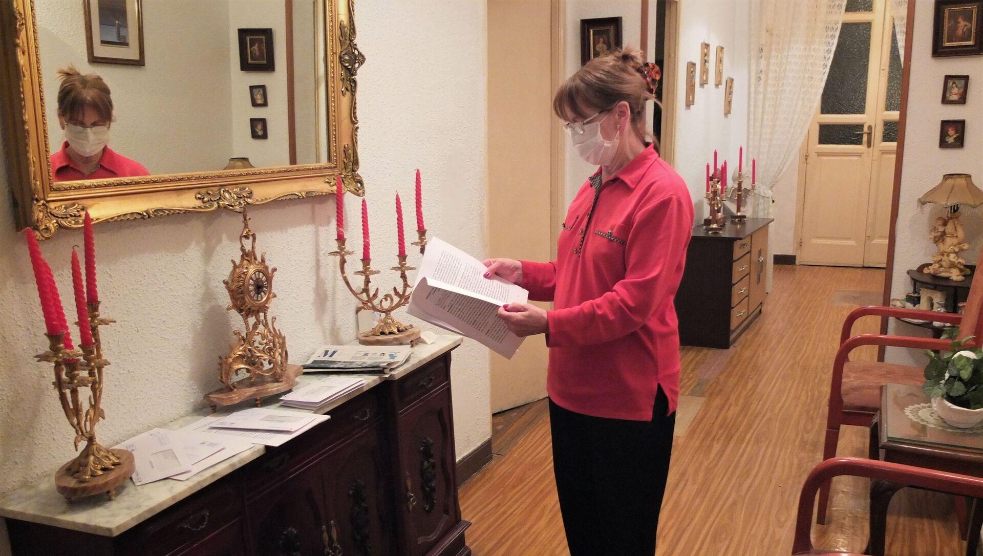 Julia Lucas, vecina del Palacio de la Infanta Carlota, en el centro de Madrid, mirando unos documentos sobre el desalojo - Sputnik Mundo, 1920, 01.12.2020