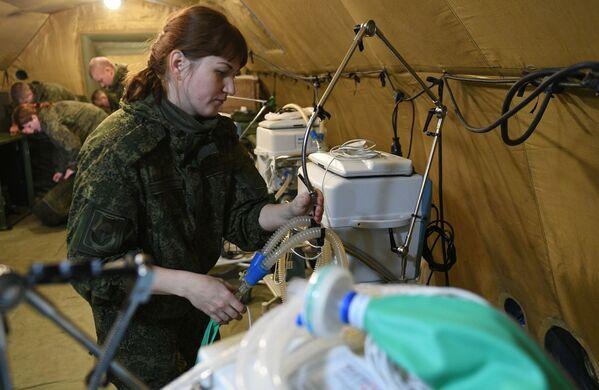 Los médicos militares están orientados en primer lugar en el servicio médico de las fuerzas de paz, pero además están dispuestos a ayudar a los residentes de la república. En la foto: militares rusos montan equipo médico en el hospital de campaña móvil cerca de Stepanakert - Sputnik Mundo