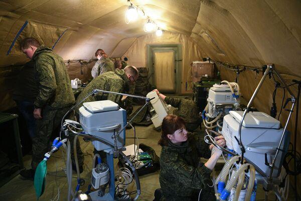 Entre los médicos militares rusos hay cirujanos, anestesistas, especialistas en cuidados intensivos, terapeutas y epidemiólogos. En la foto: militares rusos montan equipo médico en el hospital de campaña móvil cerca de Stepanakert. - Sputnik Mundo