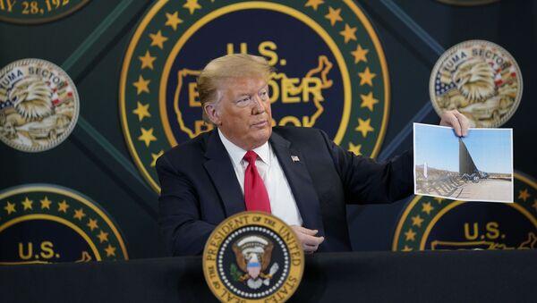 El presidente de EEUU, Donald Trump, sostiene la foto de la construcción del muro fronterizo con México - Sputnik Mundo