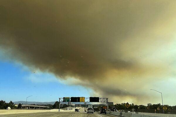 Las llamas se difunden impetuosamente debido a una baja humedad aérea y un fuerte viento, sus ráfagas alcanzan los 30 metros por segundo.En la foto: el humo sobre la carretera 22 debido a los incendios en California. - Sputnik Mundo