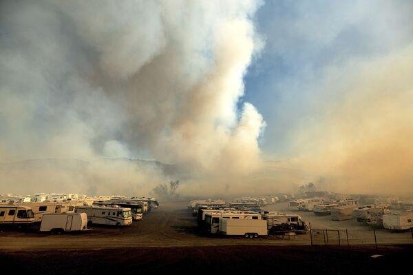 Como una prevención, las autoridades empezaron a cortar la electricidad para que no aparezcan nuevos focos debido a la ruptura de líneas eléctricas. En la foto: el humo provocado por los incendios forestales sobre el aparcamiento para autocaravanas en la orilla del lago de Irwin, en el condado de Orange, estado de California. - Sputnik Mundo