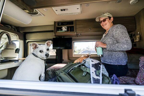 Una mujer con un perro en su autocaravana en un punto de evacuación temporal de la Cruz Roja en el condado de Orange, estado de California. - Sputnik Mundo
