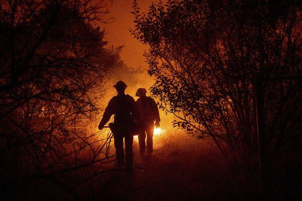 Alrededor de 50.000 hogares se han quedado sin electricidad. Para la noche del viernes 4 de diciembre esta cifra podría aumentar hasta los 270.000.En la foto: los bomberos luchan contra el incendio forestal en el condado de Orange, estado de California. - Sputnik Mundo