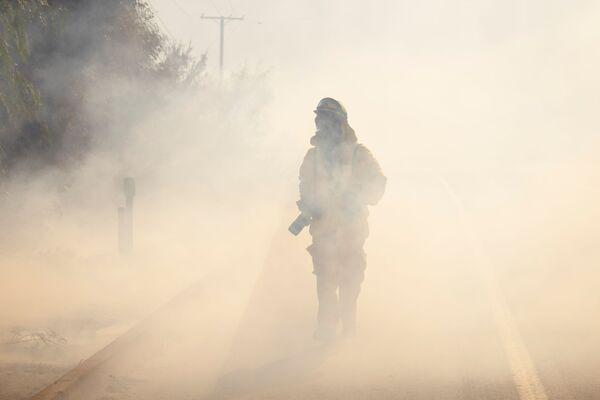 El fotógrafo de Los Angeles Times intenta atravesar el humo del incendio en el condado de Orange, California. - Sputnik Mundo