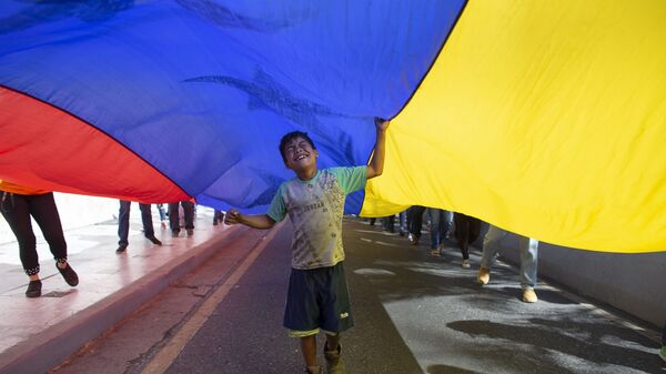 Un niño juega bajo una bandera venezolana durante una protesta contra las nuevas sanciones del gobierno de Estados Unidos. Caracas, febrero de 2020 - Sputnik Mundo