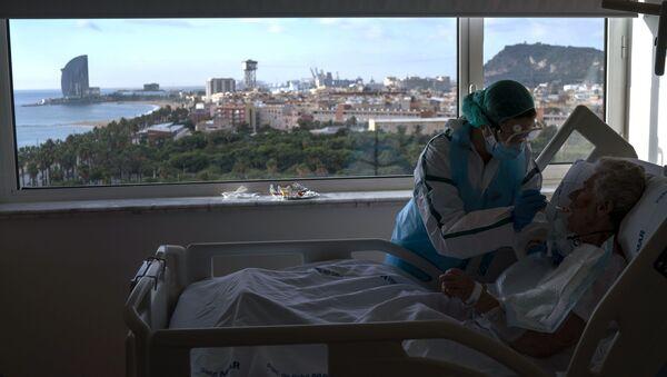 Enfermera alimenta a uno de sus pacientes en la sala COVID-19 del hospital del Mar en Barcelona. 18 de noviembre de 2020 - Sputnik Mundo