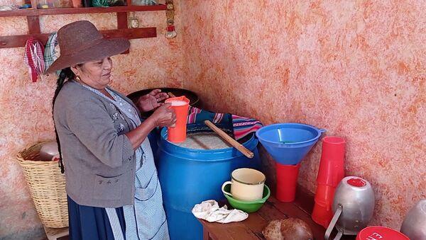 Doña Eulogia Montaño, quien tiene su chichería en Punata, sirve una jarra para sus parroquianos - Sputnik Mundo