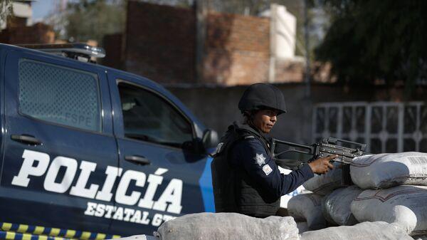 Un policía mexicano está de guardia detrás de un parapeto de sacos con arena en México - Sputnik Mundo