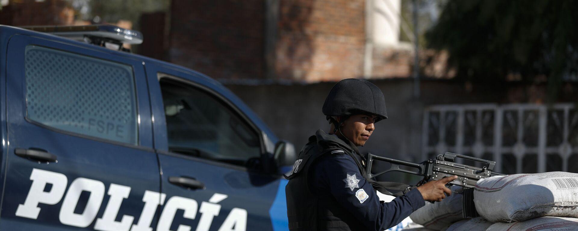 Un policía mexicano está de guardia detrás de un parapeto de sacos con arena en México - Sputnik Mundo, 1920, 23.06.2021