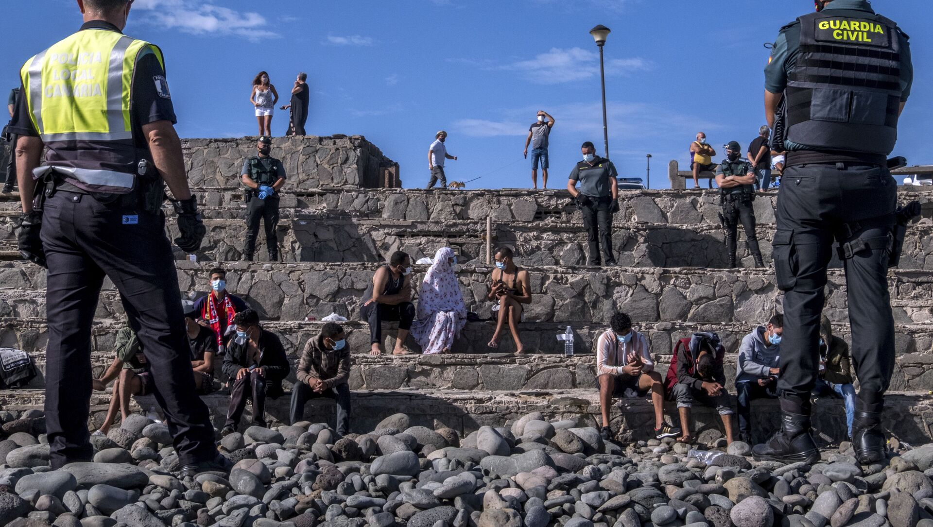 Migrantes son vigilados por la policía española después de llegar a la costa de las Islas Canarias, España. 23 de noviembre de 2020 - Sputnik Mundo, 1920, 20.01.2021