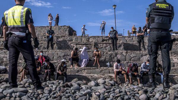 Migrantes son vigilados por la policía española después de llegar a la costa de las Islas Canarias, España. 23 de noviembre de 2020 - Sputnik Mundo