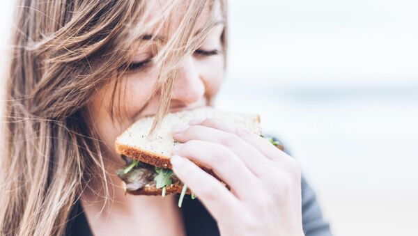 Una mujer comiendo un sándwich - Sputnik Mundo