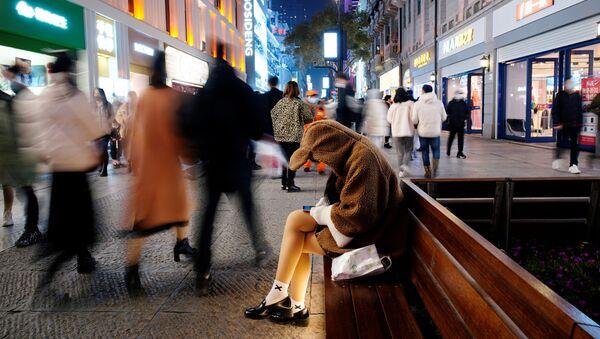 Девушка с мобильником в главном торговом районе Уханя через год после начала вспышки коронавируса, Китай - Sputnik Mundo