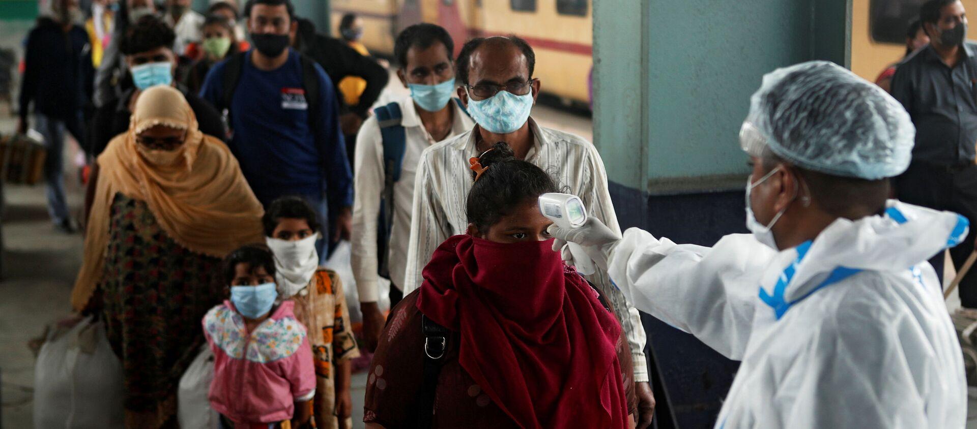 Un trabajador de la salud revisa la temperatura de los pasajeros en una estación de tren de Mumbai, la India. - Sputnik Mundo, 1920, 12.12.2020