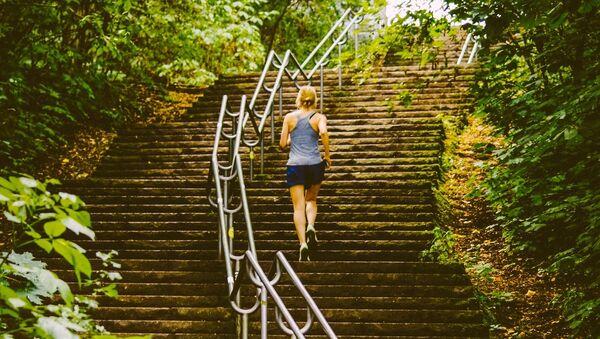 Una mujer sube las escaleras, imagen referencial - Sputnik Mundo