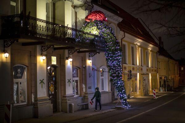 En la capital lituana, Vilnius, debido a la prohibición de las celebraciones masivas, los residentes decidieron decorar los balcones de las casas. En la foto: un balcón decorado con un árbol de Navidad y un pangolín en el centro de Vilnius.  - Sputnik Mundo