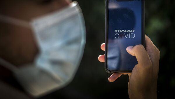 Imagen referencial de una persona utilizando la app de COVID en Portugal - Sputnik Mundo