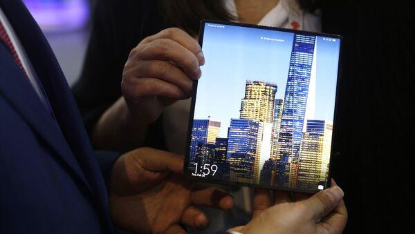 Un hombre sostiene el nuevo smartphone plegable Huawei Mate X 5G durante el espectáculo inalámbrico del Mobile World Congress, en Barcelona, España - Sputnik Mundo