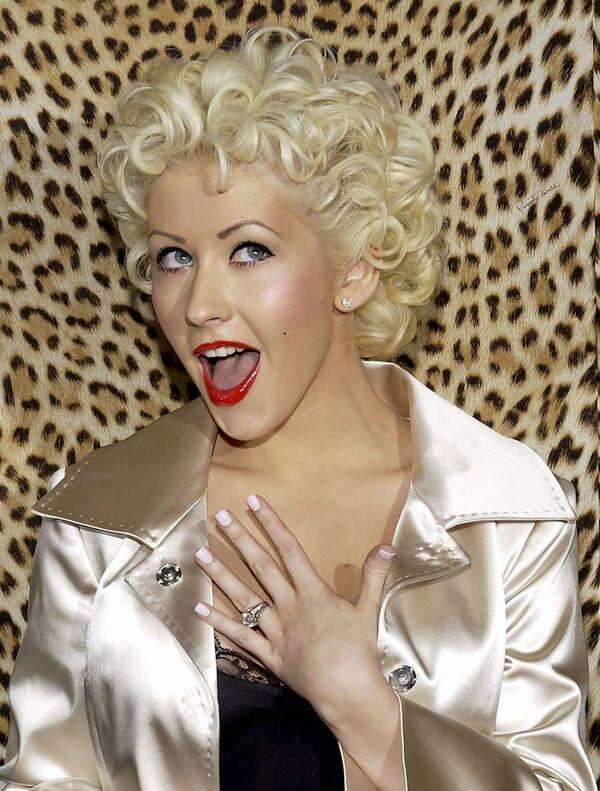 Unos años más tarde, Christina cambió inesperadamente su imagen, dejando sus 'piercings' y rastas excéntricas para convertirse en una rubia diva de Hollywood. La cantante experimentó con el jazz, el blues y el soul y pudo demostrar plenamente su hermosa voz: una soprano con un rango de cuatro octavas. En la foto: Christina Aguilera en la inauguración de la 'boutique' Rodeo Drive en Beverly Hills en 2005.  - Sputnik Mundo