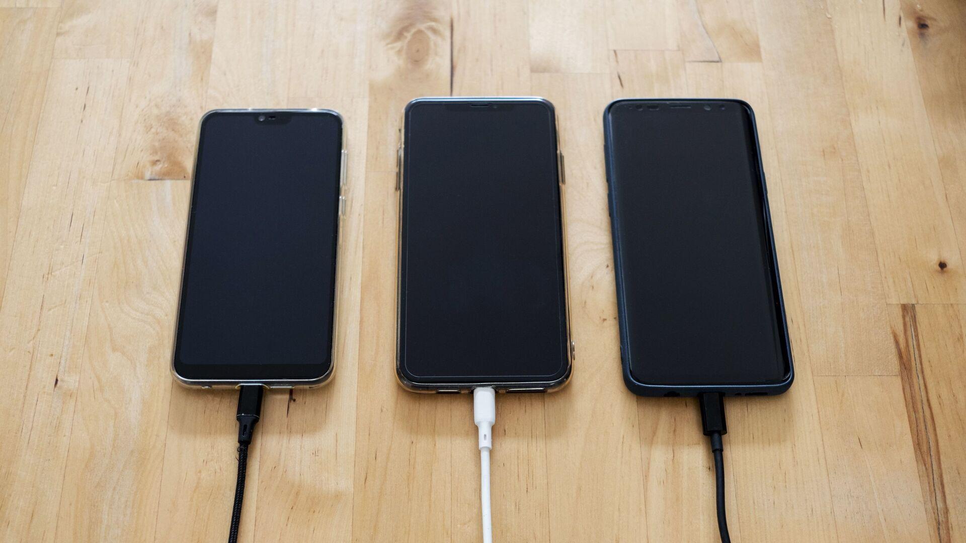 Tres 'smartphones' reciben la carga (imagen referencial) - Sputnik Mundo, 1920, 21.08.2021