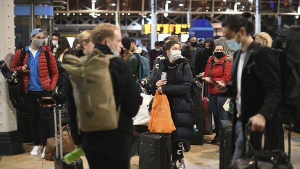 La gente espera en el vestíbulo de la estación de Paddington en Londres, después del anuncio de que la capital se someterá a las restricciones de nivel 4 contra el COVID-19. - Sputnik Mundo