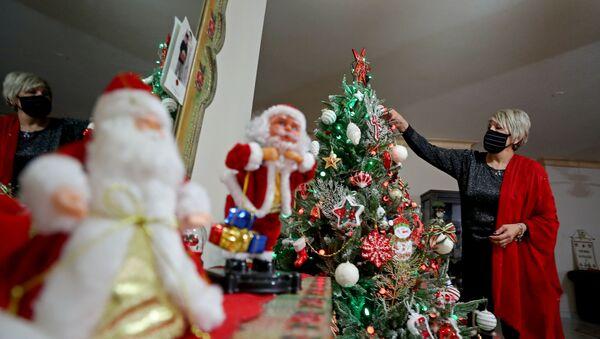 Una mujer en mascarilla decora el árbol de Navidad - Sputnik Mundo