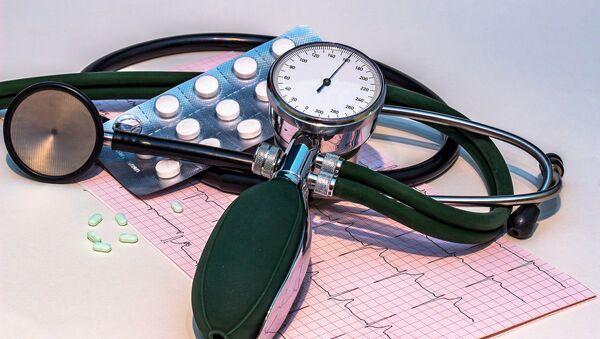 Un aparato para medir la presión arterial, unas pastillas y un gráfico de cardiograma  - Sputnik Mundo