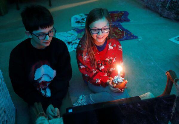 Dos niños durante un Christingle virtual, donde sostienen una vela que simboliza la luz del mundo y celebran el nacimiento de Jesucristo. Blakesley, Reino Unido. - Sputnik Mundo