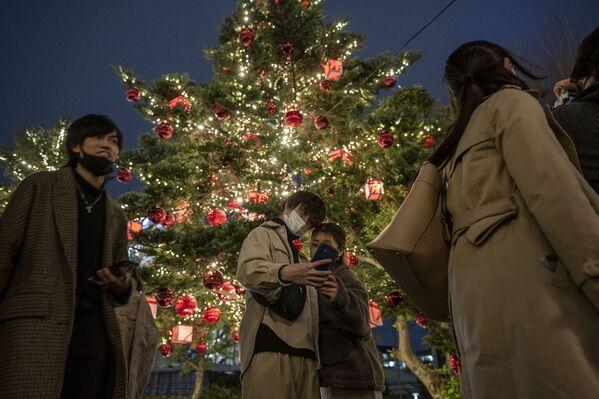 Una pareja se fotografía con un árbol de Navidad en Tokio, Japón. - Sputnik Mundo