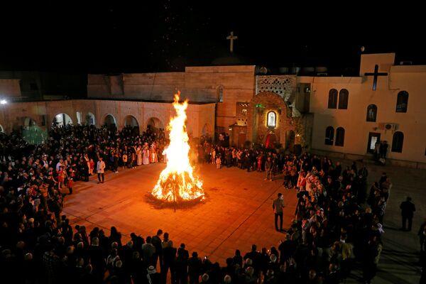 Docenas de personas rodean una hoguera durante una misa de Navidad llevada a cabo en el patio de una iglesia en Al-Hamdaniya, Irak. - Sputnik Mundo