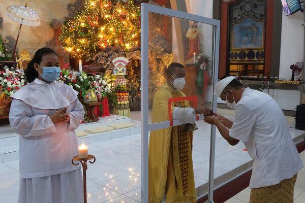 Los creyentes asisten a la misa de Navidad en una iglesia en Badung, Indonesia. - Sputnik Mundo