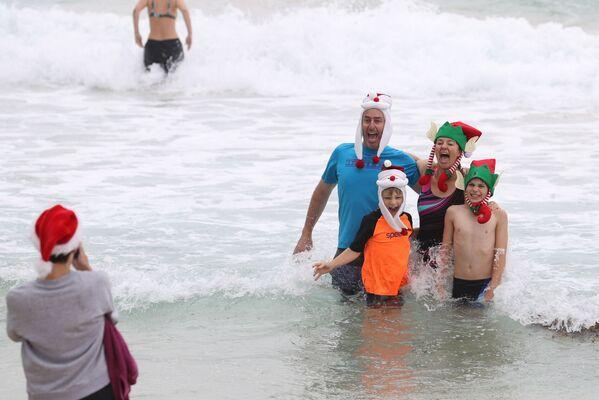 Una familia se toma fotos con gorros navideños en una playa en Sydney, Australia.  - Sputnik Mundo