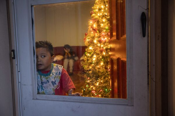 Mario, un niño migrante guatemalteco de 7 años cuyos parientes están enfermos con coronavirus, mira por la ventana en Navidad en Stamford, estado de Connecticut en EEUU. - Sputnik Mundo