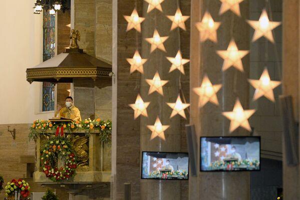 Un sacerdote celebra de manera creativa y con tecnología la misa de Navidad en la catedral de Manila, Filipinas. - Sputnik Mundo