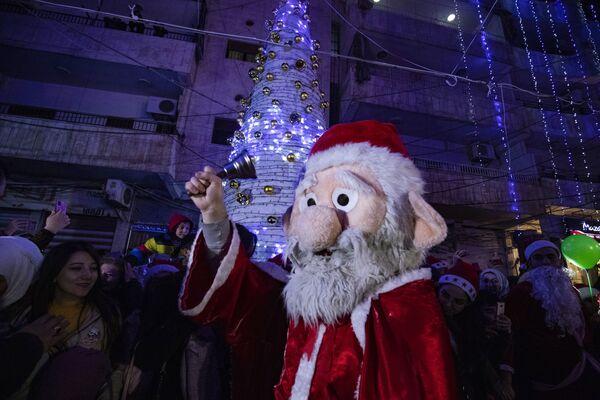Un hombre vestido de Papá Noel celebra la Navidad en la ciudad de Al-Qamishli, en el noreste de Siria. - Sputnik Mundo