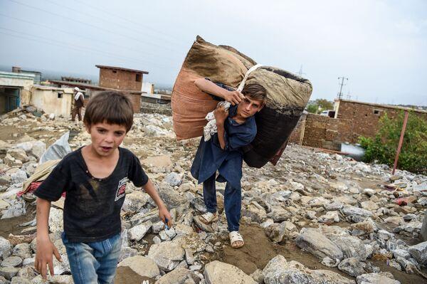 En la noche del 26 de agosto se produjo una inundación repentina en Afganistán que causó más de 150 muertes. Comenzó en la provincia de Parwan, donde fallecieron más de 100 personas, y afectó a un total de 12 provincias, incluso Kabul. Cientos de viviendas fueron destruidas, la economía sufrió enormes daños y miles de personas se quedaron sin hogar. En la foto: un vecino de un pueblo en la provincia de Parwan rescata su patrimonio que sobrevivió a una inundación. - Sputnik Mundo